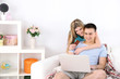Loving couple sitting with laptop and credit card