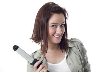 Young caucasian girl showing curling iron