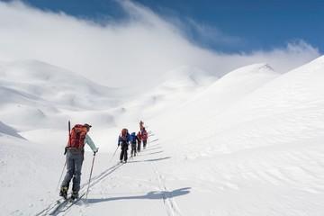 Skiers walking towards mountains