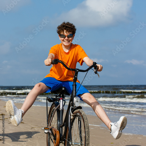 Teenage boy biking on beach