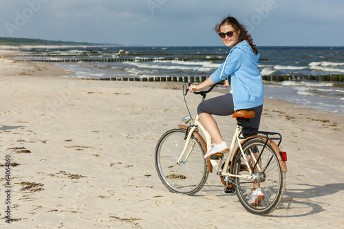 Teenage girl biking on beach