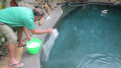 Man adds salt to his swimming pool to chlorinate the water.