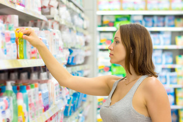 women buy shampoo in the supermarket