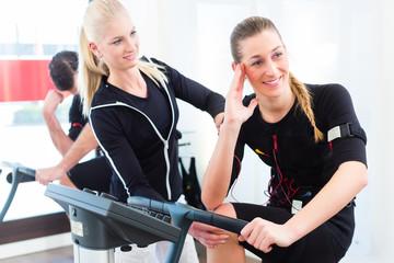 Trainer gibt EMS Training an Frau
