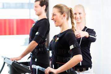 Trainer gibt EMS Training an Paar