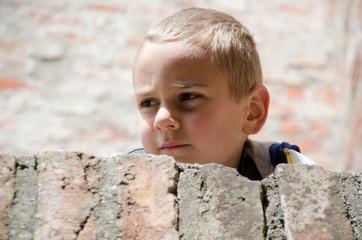 Kind schaut über eine Mauer