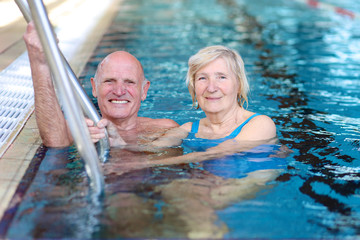 Happy couple of seniors enjoying in swimming pool