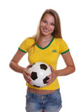 Standing woman in brazilian shirt with football
