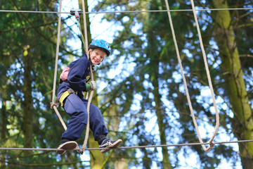 Happy school boy climbing in adventure park
