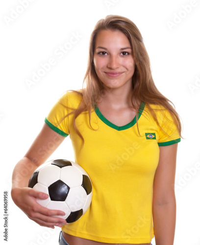 Smiling woman in brazilian shirt with football