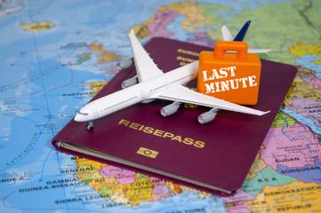 Flugzeug, Koffer und Reisepass auf Landkarte