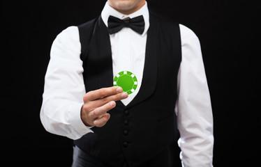 dealer holding green poker chip