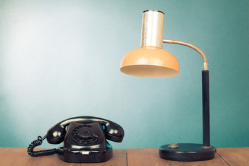Retro rotary telephone and desk lamp on table