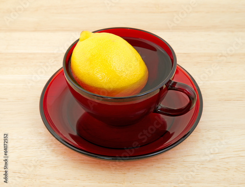 Lemon in red cup with water