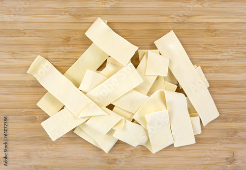 Wide egg noodles on cutting board