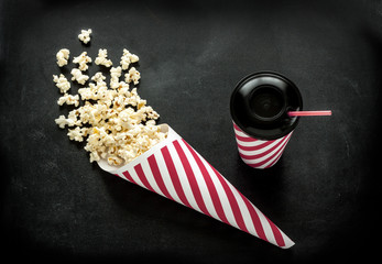 Cinema snacks - cornet popcorn and drink on black