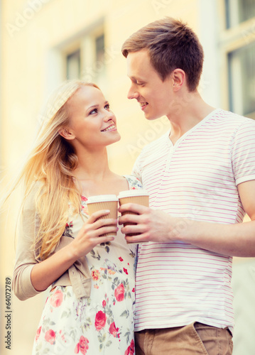 couple in the city with takeaway coffee cups