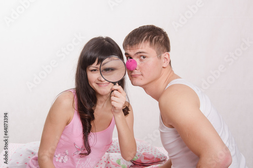 Girl with magnifying glass, guy clown nose
