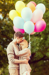 couple with colorful balloons kissing in the park