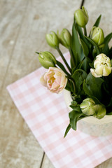 Bouquet of delicate pink tulips on the tablecloth