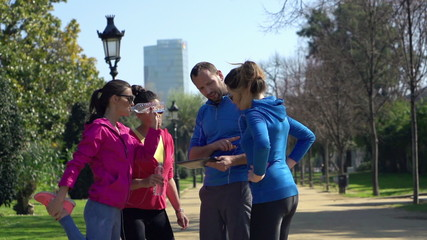 Trainer explain something to sportwomen in park, slow motion