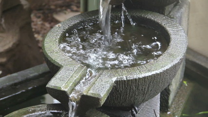 Water falling into stone bowls in a garden water feature.