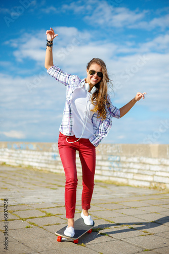 smiling teenage girl riding skate outside