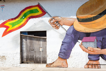 Man with hat and house and a Colombian flag in his hands