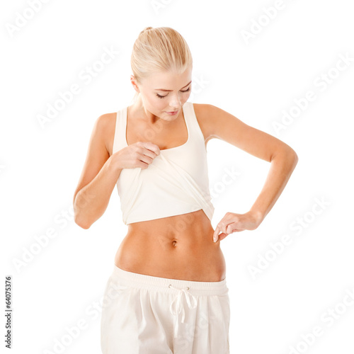 fit woman measuring fat level on her waist