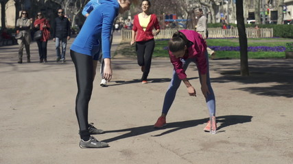 Women exercising, stretching in city, super slow motion