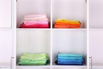 White shelves with colored clothing close up