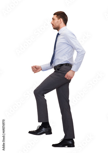 serious businessman stepping on imaginary step