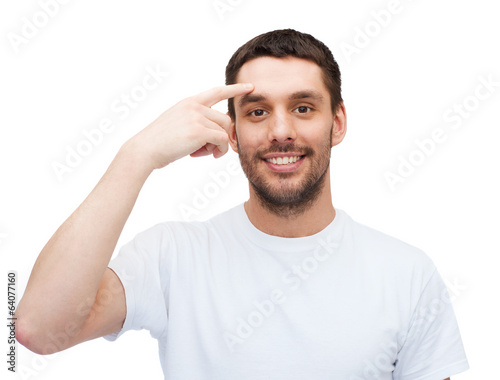 smiling young handsome man pointing to forehead