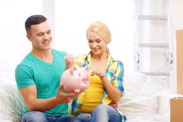 smiling couple with piggybank in new home