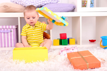 Cute little boy with present boxes in room