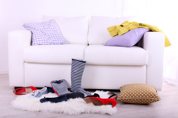 Messy colorful clothing and shoes on  sofa on light background