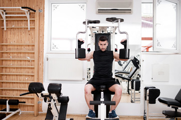 Handsome man working out at gym, daily chest exercise routine