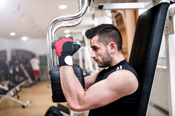 sporty man doing chest exercise at gym, daily workout routine
