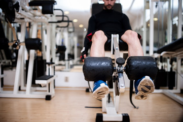 Gym fitness center with young man working out the legs