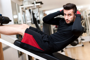 Handsome muscular man doing sit-ups on a incline bench at fitnes