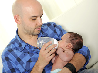 young father feeding newborn baby with milk bottle on couch