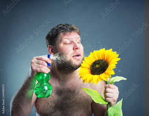 Portrait of man with sunflower, studio shoot
