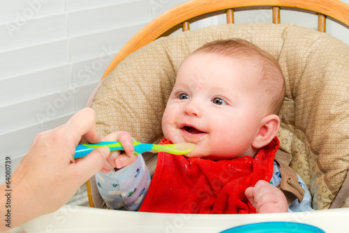 Baby eating homemade organic pureed food from spoon