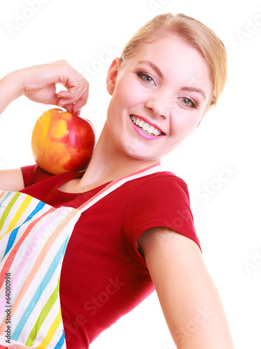 Happy housewife or chef in kitchen apron holding apple isolated