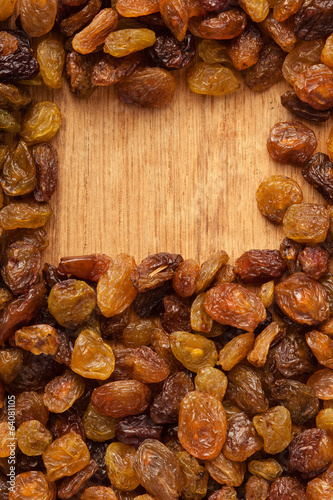 Diet healthy food. Border of raisin on wooden background
