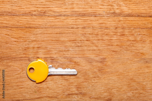House key with yellow plastic coats caps on table