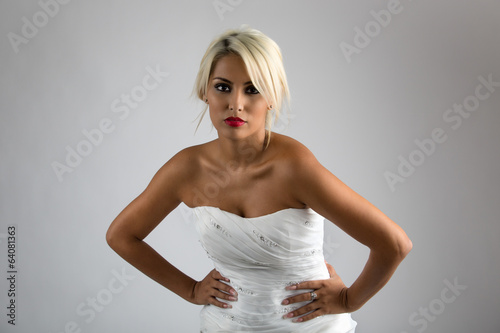 The beautiful young woman posing in a wedding strapless dress.Be