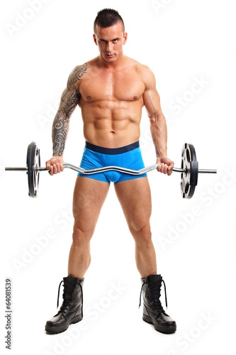 Handsome muscular man standing poses with dumbbell