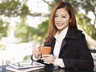 woman sitting by window holding coffee cup smiling
