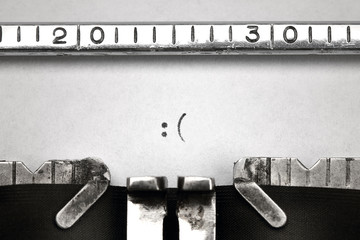 Sad smiley sign written on an old typewriter